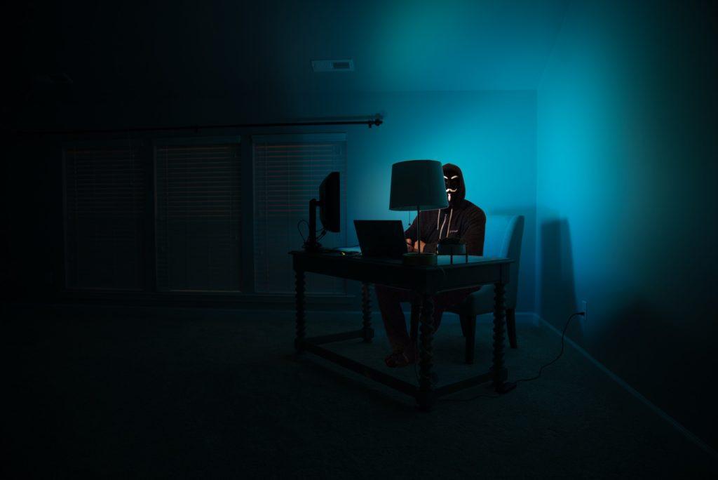 hacker dentro de uma sala escura